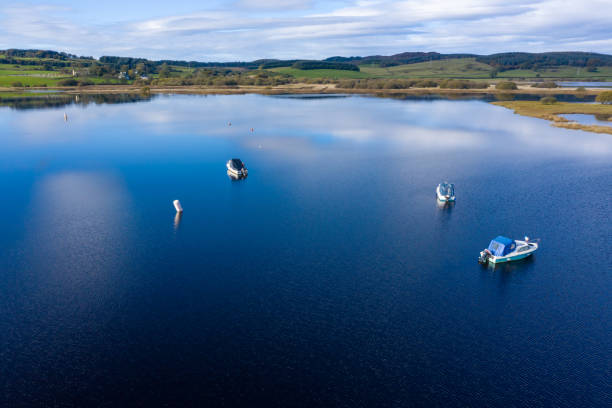 The aerial view of calm water in rural Dumfries and Galloway south west Scotland The view from a drone of a stretch of Scottish river that is flowing out out of a loch. It is early autumn and autumn colours are stating to show on the plants and trees. johnfscott stock pictures, royalty-free photos & images