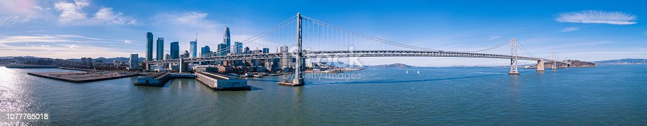 The aerial drone scenic view of San Francisco, California. The extra-wide stitched panorama of the Oakland Bay Bridge over the San Francisco Bay, between Downtown and Treasure Island. Northern California, USA