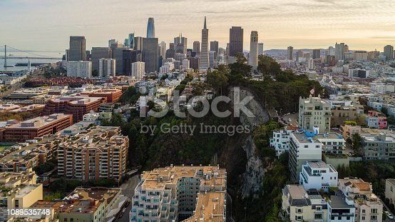 Remote aerial panoramic view of San Francisco Downtown over the residential area at sunset. The skyline includes the major buildings Salesforce Tower, Transamerica Pyramid, Lumina, Coit Tower, and more. Northern California, USA