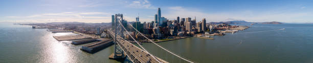 The aerial view of San Francisco Downtown over the Oakland Bay Bridge The aerial drone scenic panoramic view of San Francisco Downtown over the Oakland Bay Bridge with the car traffic. Northern California, USA. san francisco bay stock pictures, royalty-free photos & images