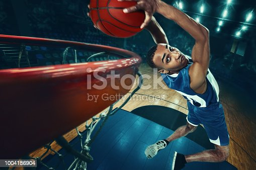 The african man basketball player jumping with ball on black background