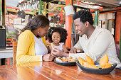 The Afro family of mom, dad and daughter smile because the food arrived and they are delicious empanadas and chicharrones that they bring to the table of the restaurant of typical Colombian food