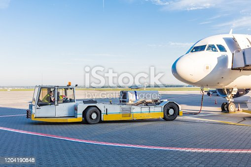 Pushback tractor standing next to the airplane. Airport ground crew at work.