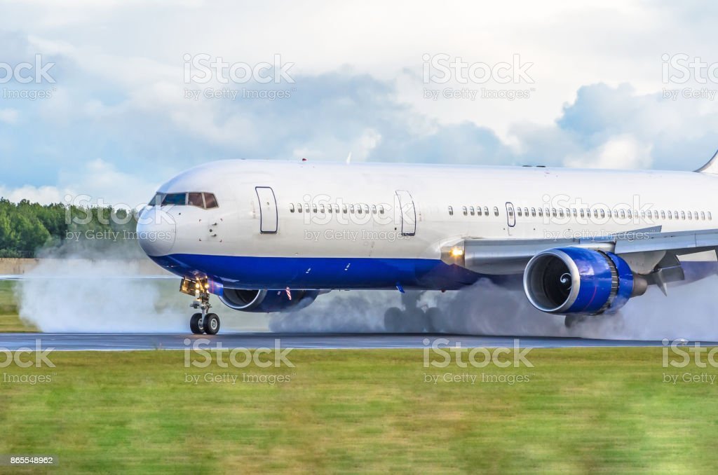 The airplane with the reversed engine on the wet runway. stock photo