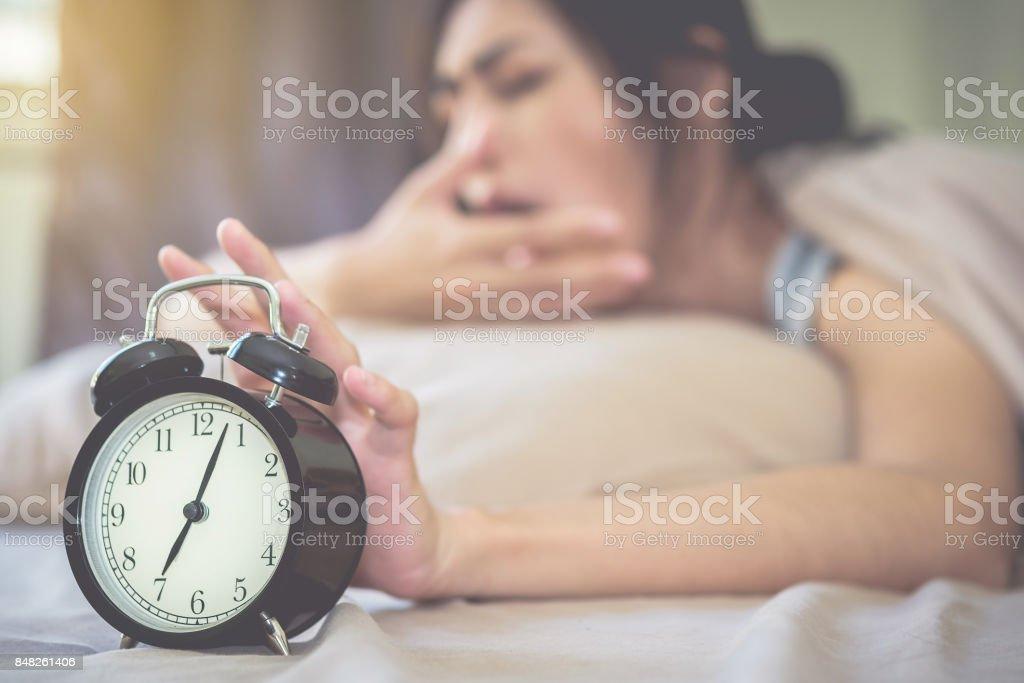 O despertador está a tocar bem alto, com a mulher também sonolenta como plano de fundo desfocado. Focar o despertador. - foto de acervo