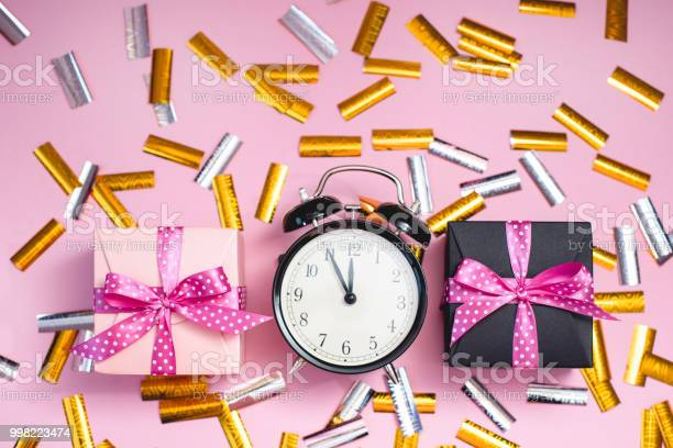 The alarm clock, which shows almost midnight among the multicolored confetti and present boxes.