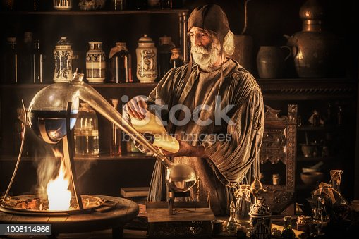 Medieval alchemist distilling in his laboratory
