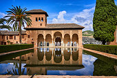 Alhambra in Granada, Spain, Oct 19, 2019. El Partal. A large central pond faces the arched portico behind which stands the Tower of the Ladies. The Alhambra, palace and fortress complex  showing the last flowering of Islamic palaces built for the last Muslim emirs in Spain during the decline of the Nasrid dynasty. After the conclusion of the Christian Reconquista in 1492, the site became the Royal Court of Fernando and Isabel La Católica, and the palaces were partially altered in the Renaissance style.