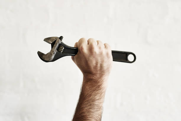 The all powerful monkey wrench Shot of an unrecognizable handyman holding up a monkey wrench adjustable wrench stock pictures, royalty-free photos & images