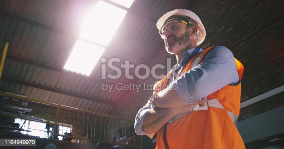 Low angle shot of a confident mature engineer in an industrial place of work