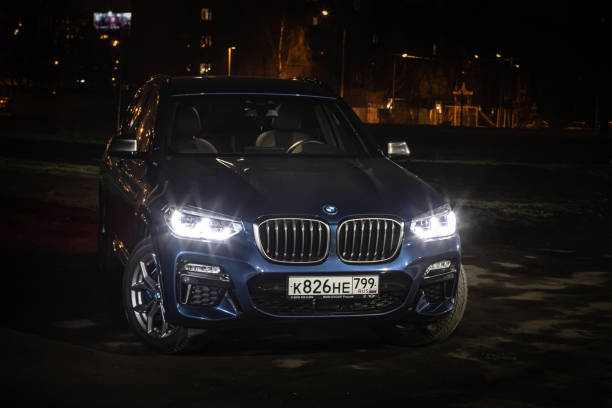 The all-new BMW X3. Blue crossover stands on the street at night. Premium German SUV front view. stock photo