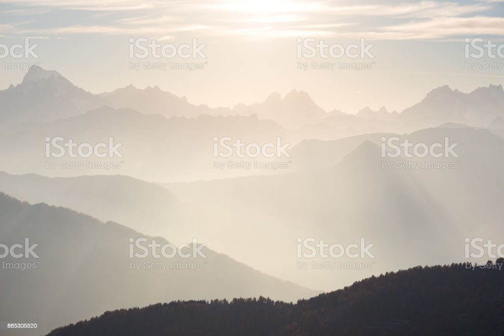 The Alps in soft backlight. Toned mountain range of the Massif des Ecrins National Park, France, arising higher than 4000 m altitude from the alpine arc. Telephoto view at sunset. stock photo