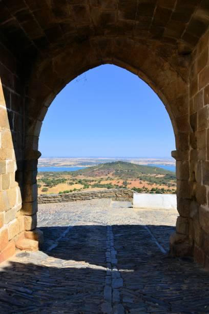the alqueva dam seen through a gate in the medieval walls of monsaraz, alentejo, portugal - fotos de barragem portugal imagens e fotografias de stock