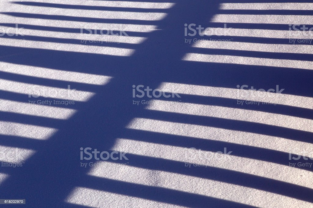 The alternation of light and dark bands in the snow. stock photo