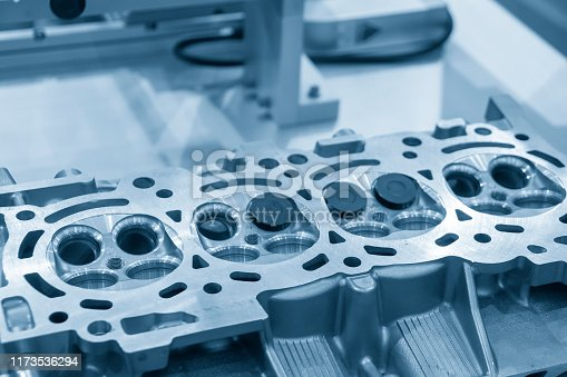 istock The aluminium casting cylinder head parts in the assembly process with the exhaust and intake valve in the light blue scene. 1173536294
