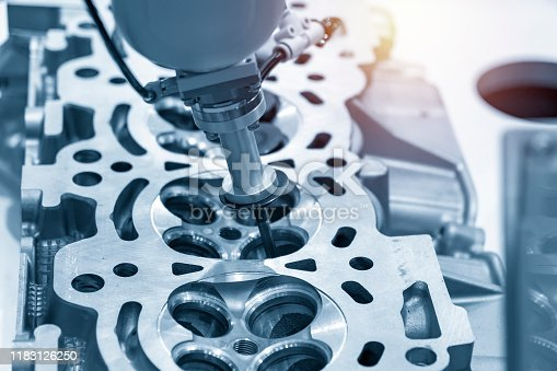 936360074 istock photo The aluminium casting cylinder head parts in the assembly process with the exhaust and intake valve parts in the light blue scene. 1183126250