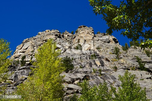 The immense and beautiful granite walls of the Tetons canyons are stunning against a brilliant blue sky.