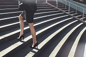 Cropped shot of a businesswoman walking up urban steps