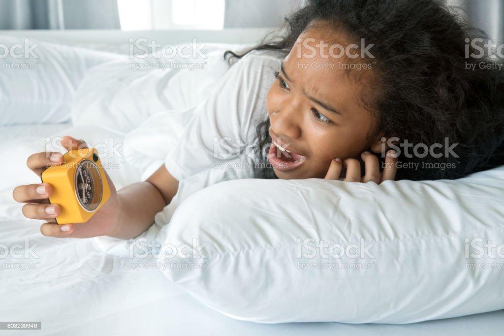 A americana linda garota olhando relógio despertador com acorda tarde e pânico em uma manhã no quarto de cama branco limpo - foto de acervo