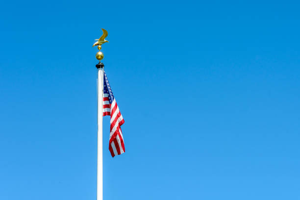 The American flag dangling at full-mast on a white pole topped with a golden eagle on ball ornament against deep blue sky. The flag of the United States of America dangling at full-mast on a white pole topped with a golden eagle on ball ornament against deep blue sky. flagpole stock pictures, royalty-free photos & images