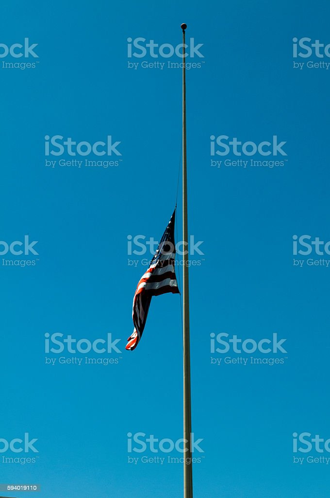 The American flag fly on half staff stock photo