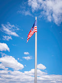 istock The American flag waving on the pole on blue sky with white clouds backgrounds 1223071998