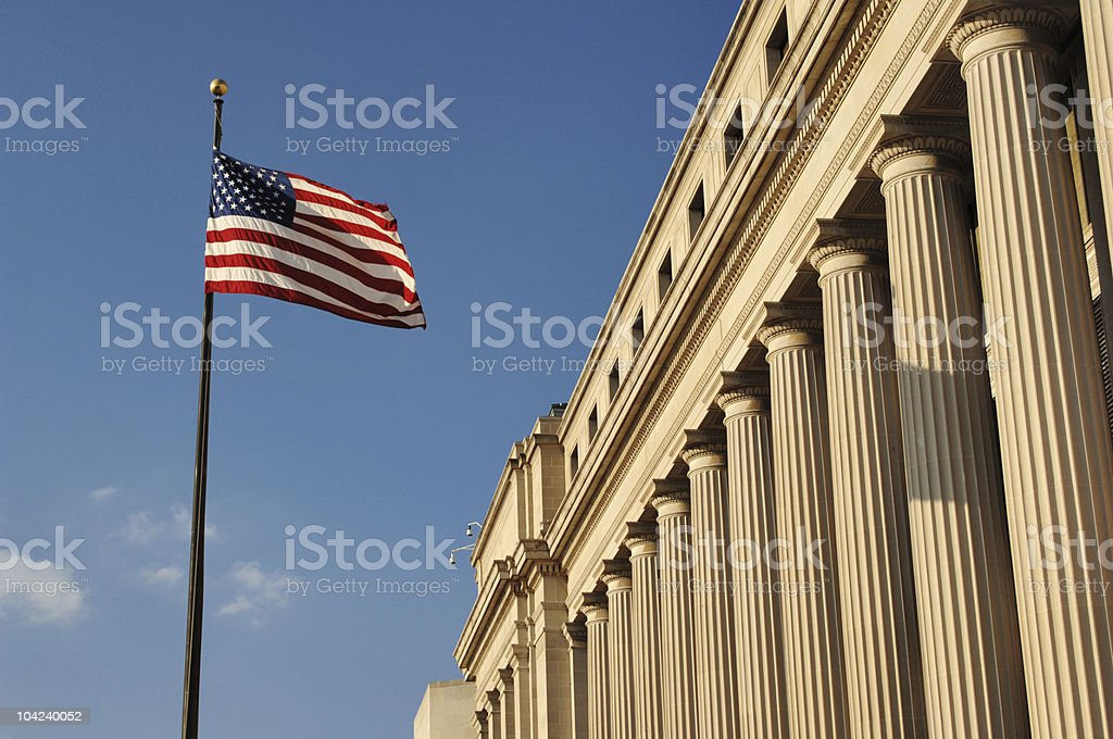 The American flag waving outside a building in Washington DC stock photo