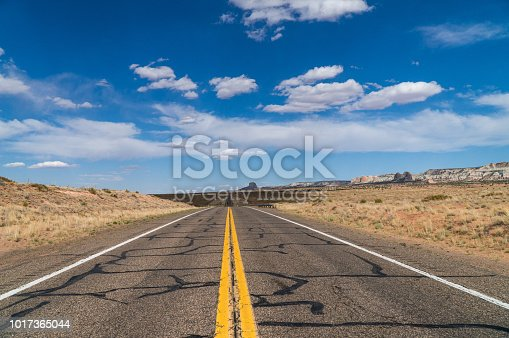 American asphalt road from low angle with mountains on background.