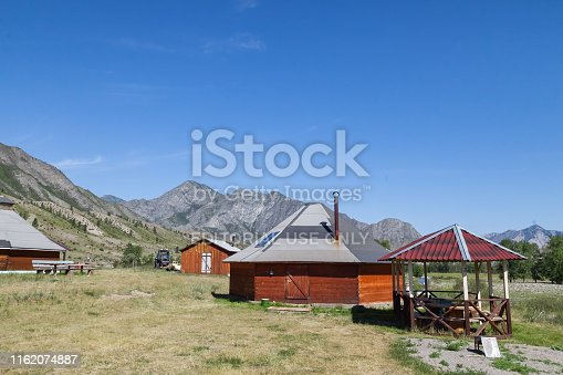 istock The ancient antique ail house from wood is round-shaped with a chimney on top of the center, for the nomadic indigenous people in the Altai Mountains with green trees and picturesque scenery. 1162074887