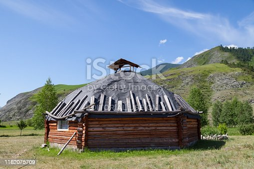 istock The ancient antique ail house from wood is round-shaped with a chimney on top of the center, for the nomadic indigenous people in the Altai Mountains with green trees and picturesque scenery. 1162075709