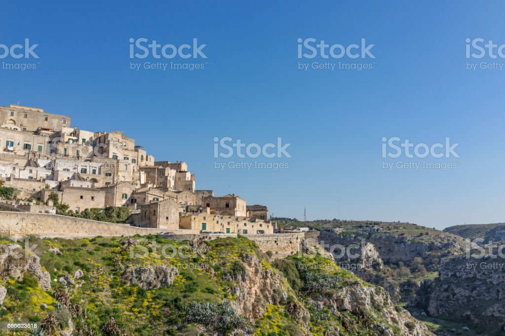 The ancient ghost town of Matera (Sassi di Matera) in beautiful yellow flower in daylight, southern Italy royalty-free stock photo