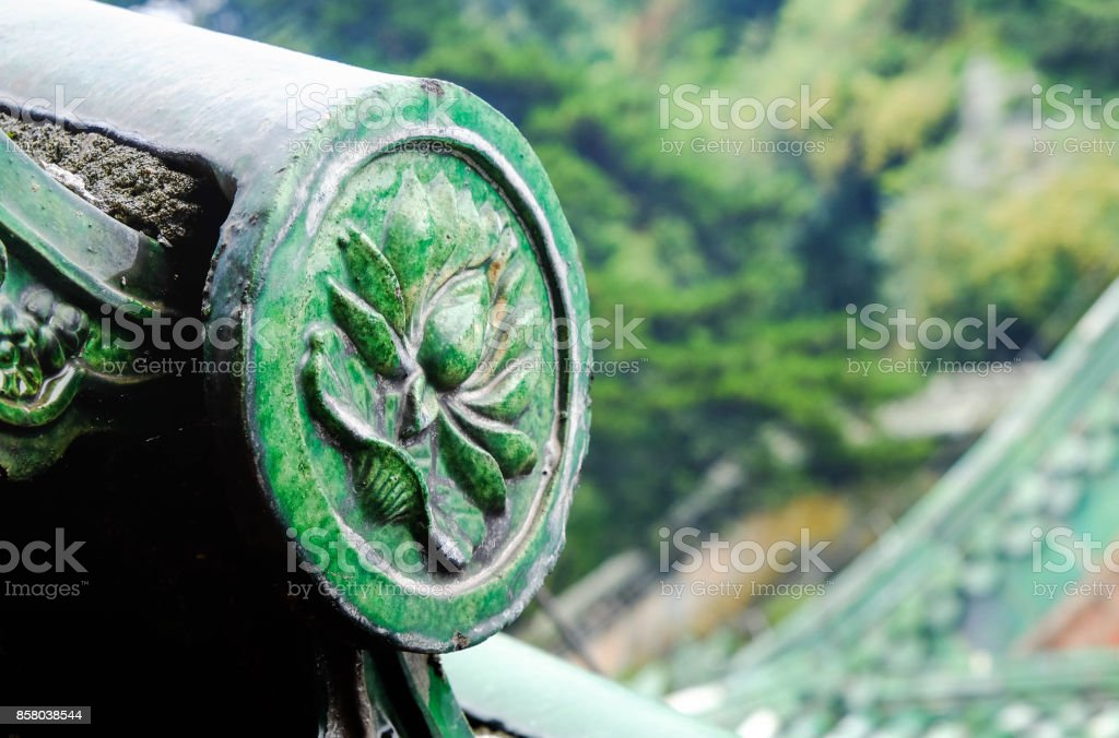 The ancient green glazed tile roof and decorate with the lotus stock photo