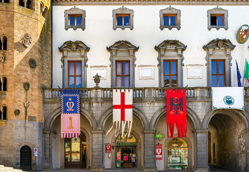 Orvieto, Umbria, Italy, May 27 -- Piazza della Repubblica and the ancient Palazzo Comunale (Town Hall) in the heart of the medieval town of Orvieto in central Italy, decorated with the flags of the four historic districts of the city. To the left a glimpse of the decagonal bell tower of the St. Andrews church. With a population of just 20,000 people, Orvieto is considered one of the most beautiful cities of art in Italy, founded since the Etruscan and Roman times on the flat top of a large butte of volcanic tuff. This same material was used for the construction of almost all the medieval houses and churches of Orvieto, as well as its famous Gothic-style Cathedral. Image in high definition format.