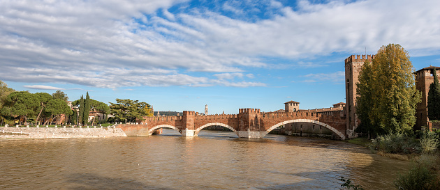 Verona, Veneto, Italy - November 14th, 2012: The Castelvecchio bridge (italian: Ponte di Castelvecchio) or Scaliger Bridge (Italian: Ponte Scaligero) is a fortified bridge in Verona over the Adige river, near Castelvecchio (Old Castle), the castle of Verona (UNESCO world heritage site), It is the most important military construction of the Scaliger dynasty that ruled the city in the Middle Ages. Castelvecchio is now home to the Castelvecchio Museum