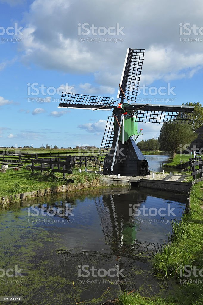 The ancient windmill is reflected in pond royalty-free stock photo