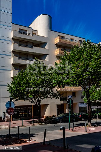 The area near Lyon Part Dieu station and near the tram stop for the airport express. There are modern apartment blocks on Cours gambetta with late afternoon sunlight on their balconies.