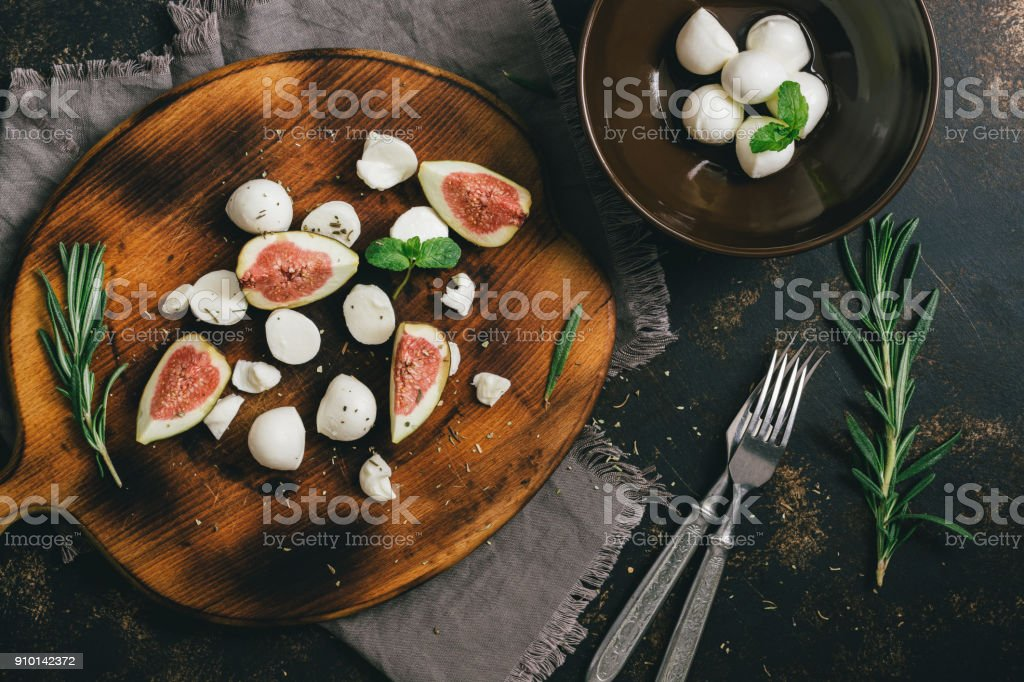 The appetizer with figs and cheese on a cutting Board. stock photo