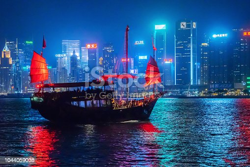 HONG KONG - September 23, 2018: The Aqua Luna sailing in Hong Kong Downtown, financial district, at night. The red boat is a Chinese Junk operating in Victoria Harbour