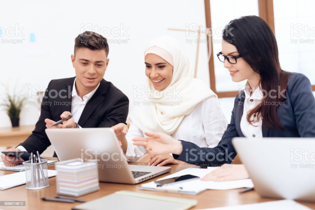 The Arab woman in hijab works in the office together with her...