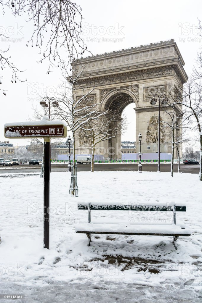 The Arc de Triumph by a rare snowy day in Paris, with a public bench covered in snow in the foreground stock photo