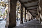 The arcades of Passeig Picasso, stately and French-inspired, are in the basement of several buildings housing built in the early twentieth century to the petty bourgeoisie of Barcelona, Catalonia, Spain