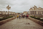 Skopje / North Macedonia, May 12 2019: The Archaeological Museum of Macedonia and Macedonian people walking on the Stone Bridge; a main historical tourist attraction that originates from the Ottoman period