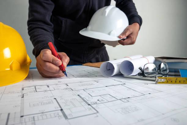 el arquitecto está trabajando para diseñar el edificio en el escritorio de la oficina. - ingeniero fotografías e imágenes de stock
