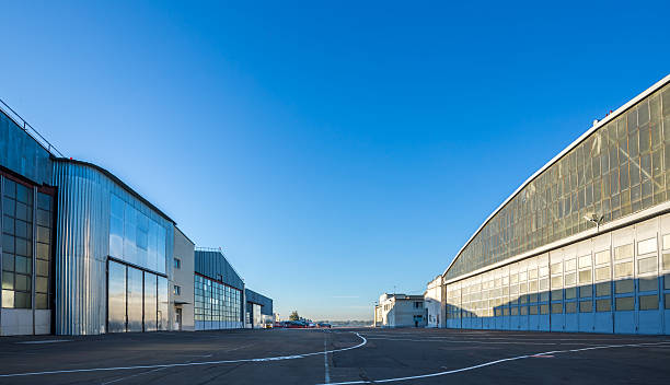 The area between aircraft hangars The area between aircraft hangars. Buildings are large and gray on the road with aviation markings. The weather is sunny with blue clear sky. military base stock pictures, royalty-free photos & images