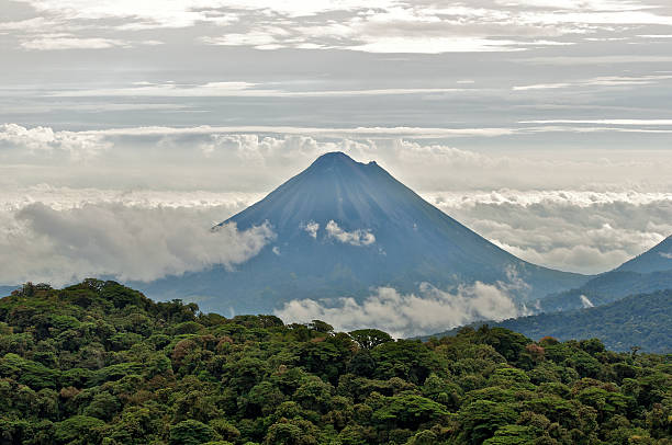 The Arenal Volcano between layers of cloud The Arenal Volcano seen from the Monteverde Cloud Forest. arenal volcano stock pictures, royalty-free photos & images