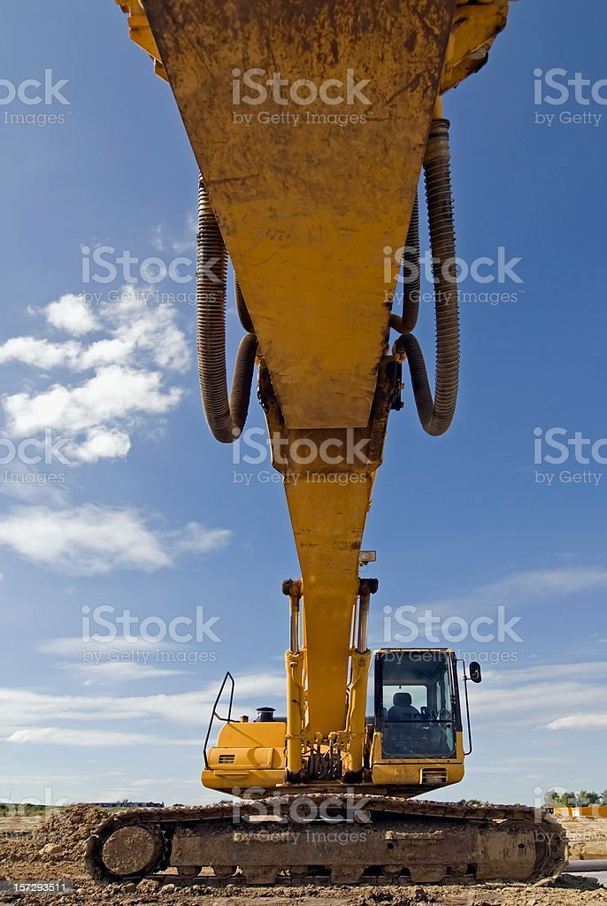 The arm of an excavator extends towards the viewer royalty-free stock photo