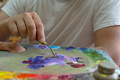 the artist's hands are kneaded with paints on a palette of palette knife