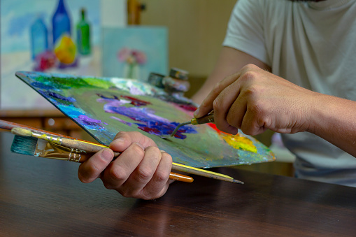 577949148 istock photo the artist's hands are kneaded with paints on a palette of palette knife 960027666