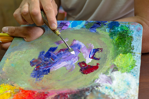 577949148 istock photo the artist's hands are kneaded with paints on a palette of palette knife 960027906