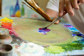 The artist's hands are mixing paints with a palette